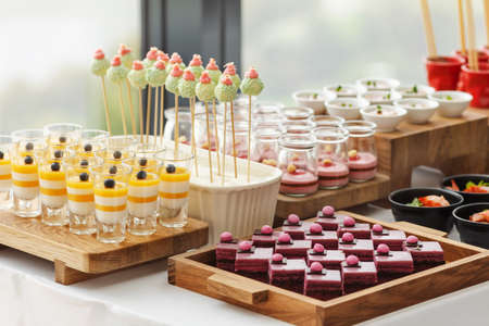 Assorted tasty sweets and pastry served on wooden trays at restaurant buffet
