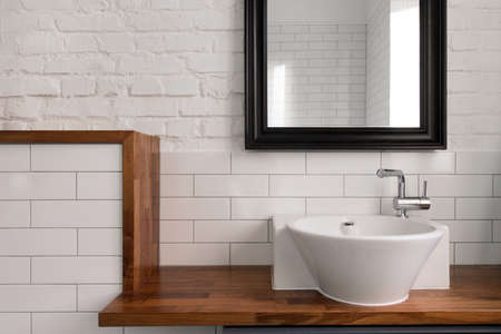 Big mirror with dark frame hanged on white painted and tiled brick wall over wooden counter around ceramic sink in light washroom with interior design in loft style
