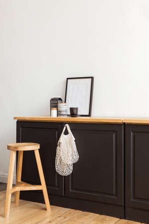 Modern cupboard with cotton bags and various decorations placed near wooden stool against white wall in stylish apartment