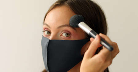 Woman in protective mask is making make-up and looking at camera on a white background