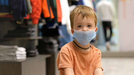 Kid boy in a protective medical mask sits and waits for parents while shopping in a clothing store