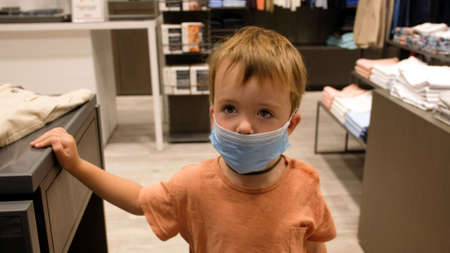 Kid boy in a protective medical mask waits for parents while shopping