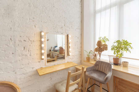 Interior of cozy light room with comfortable furniture and mirror in modern home
