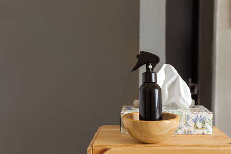 Bowl with black sprayer of detergent and box with tissues placed on wooden shelf at home on a dark gray background