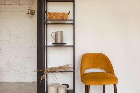 Comfortable chair placed near shelves with various accessories in cozy room at home 版權商用圖片