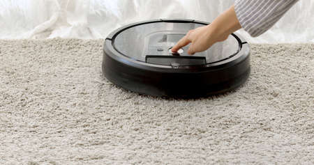 Woman sets the program to the robot vacuum cleaner