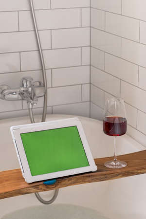 Glass of wine on shelf near tablet with chromakey while relaxing in bathtub at home