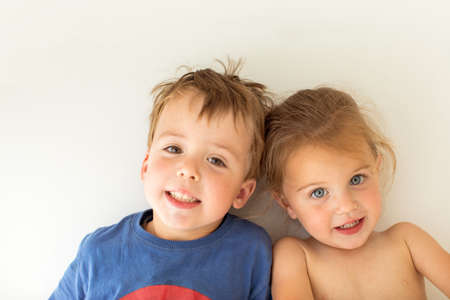 Adorable brother and sister smiling and looking at camera while leaning on white wall Banque d'images