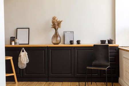 Various decorations placed on black cupboards near chair and stool in stylish room