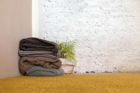 Pile of knitted warm coverlets and potted plant placed in corner of cozy room