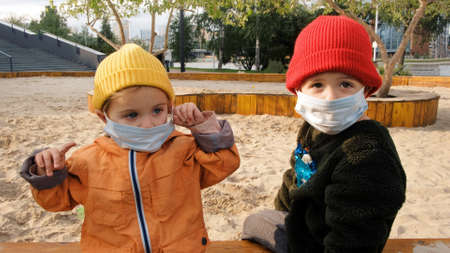 Child boy and girl walking outdoors with face mask protection. Children in protective masks walk in a large sandbox and play together. Kids sits on bench