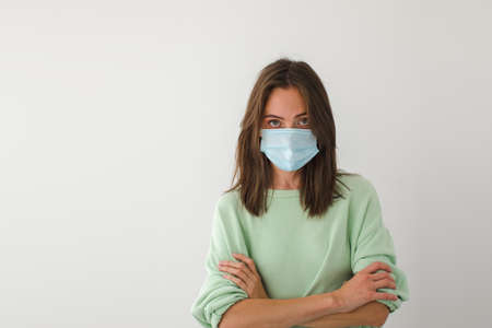 Portrait beautiful young woman in medical face mask with crossed arms