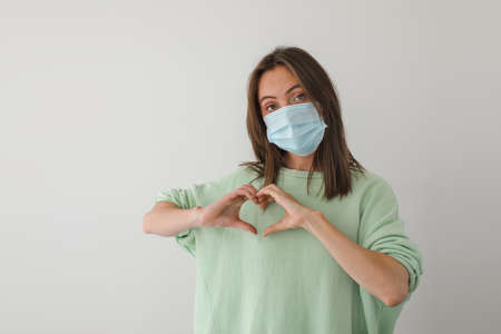 Happy woman in protective medical face mask holds hands in form of heart symbol white