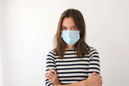 Woman in a medical protective mask has her arms crossed on white