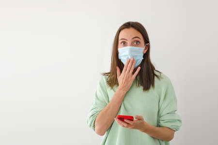 Astonished female in medical mask looking at camera and covering mouth while browsing smartphone against gray background during epidemic Banque d'images