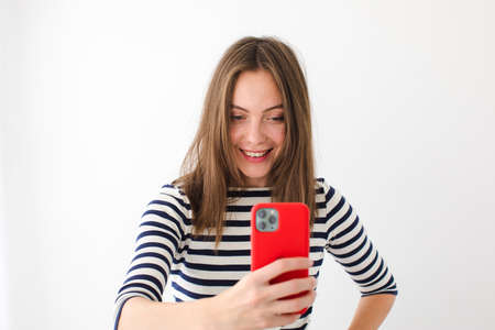 Smiling cute woman in a vest makes a photo on a red smartphone while standing on a white background Banque d'images