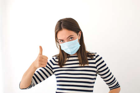 Beautiful caucasian young woman in disposable face mask showing thumb up white background