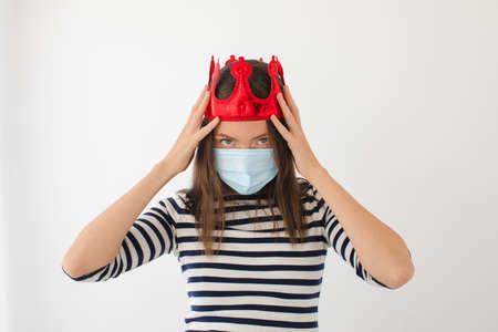 Serious young female in casual clothes and protective mask with red crown on head looking at camera representing coronavirus pandemic concept