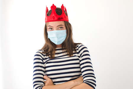 I have a crown. Woman in a red crown and a protective mask looking at camera. Crowned person fell ill with the virus white background Banque d'images