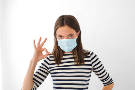 Adult woman in striped t shirt and medical mask looking at camera and gesturing OK during epidemic against gray background