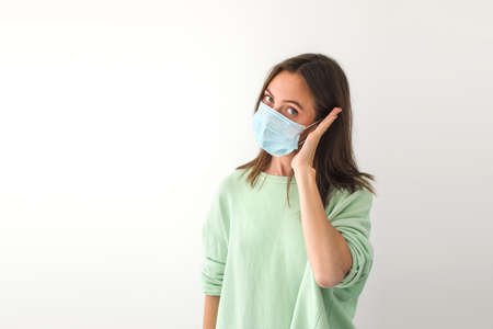 Adult female in medical mask keeping palm near ear and looking at camera while pretending to make call during pandemic against gray background