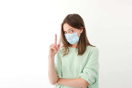 Serious female wearing medical mask during coronavirus standing on white background at home and pointing up with index finger while looking at camera