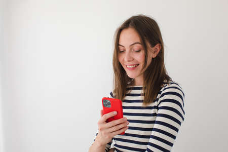 Cute female reading messages on cellphone while standing on a white background Stock fotó