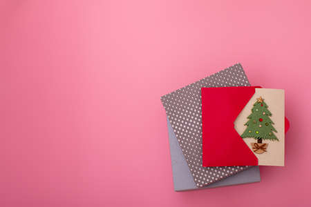 Flatlay gift boxes with homemade cards with christmas tree on pink background