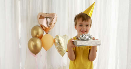 Funny kid in yellow birthday hat and t-shirt holds paper present box and shakes standings against coloured balloons closeup Banque d'images
