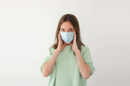 Adult female adjusting face mask and looking at camera during pandemic against gray background Stockfoto