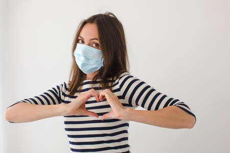Adult woman in face mask looking at camera and gesturing heart near chest during pandemic against gray background