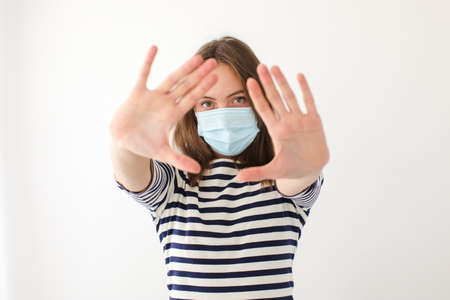 Adult female in medical mask looking at camera and gesturing stop while trying to get protection from coronavirus against gray background