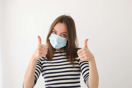 Adult female in medical mask looking at camera and showing thumb up gesture against gray wall during epidemic