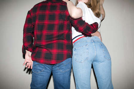 Low angle back view of crop young boyfriend and girlfriend wearing stylish clothes hugging on gray background in studio