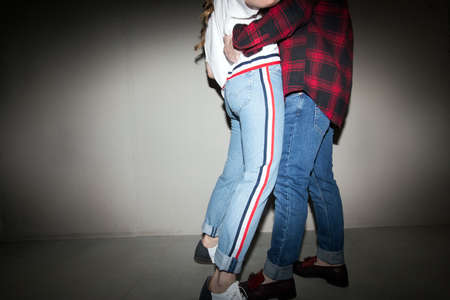 Low angle side view of crop couple of hipsters in street style outfit embracing in dark studio
