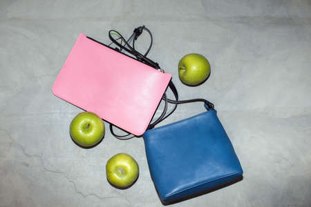 Top view of trendy blue and pink leather handbags arranged on table with fresh green apples showing concept of eco friendly materials Stockfoto
