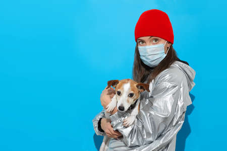 Studio shot of young woman wearing medical face mask standing together with her dog isolated over blue