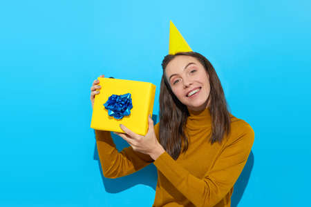 Cute woman in party hat holding yellow gift box in studio on blue background Stockfoto