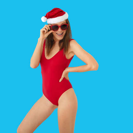 Positive slim female in red swimsuit and Christmas hat touching stylish sunglasses while standing against bright blue background