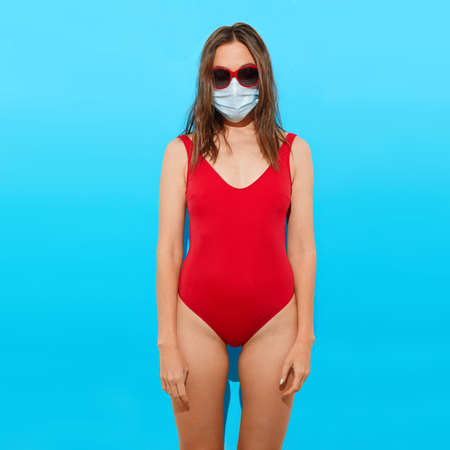 Young female in red swimwear and sunglasses wearing protective mask for coronavirus prevention standing against blue background