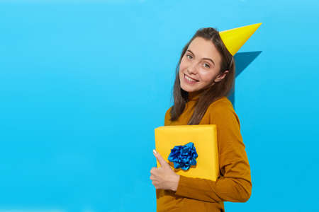 Happy female in party hat holding gift box wrapped in yellow paper and looking at camera while standing against blue background in studio Stockfoto