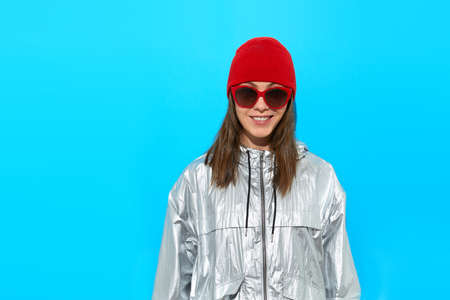 Cheerful young active female in trendy sunglasses wearing stylish gray sportive jacket and red knitted hat standing against blue background