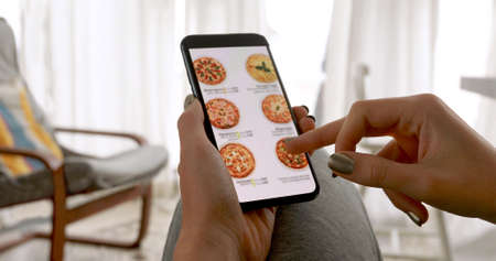 Woman browsing smartphone screen ordering pizza at home online