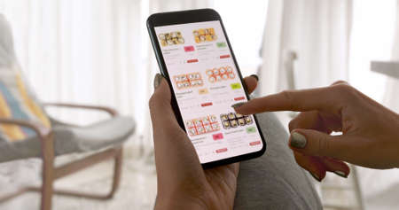 Unrecognizable woman holding phone with app delivery sushi food on screen at home