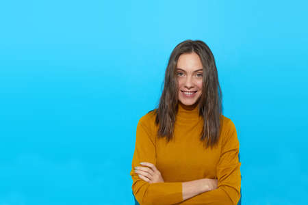 Charming female in casual turtleneck standing with crossed arms on blue background in studio and happily looking at camera