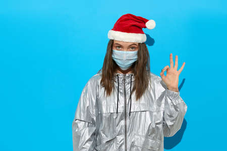 Serious female wearing Santa hat and protective mask standing on blue background in studio and showing OK gesture while looking at camera Stockfoto