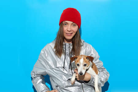 Female hipster in warm outfit standing with cute dog on blue background in studio and looking at camera Stockfoto