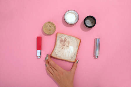 Top view of crop unrecognizable female with toast and various cosmetic products arranged on pink background in studio