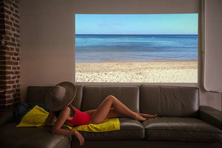Woman pretends to sunbathe on a fake beach looking at the sea of a projector during a pandemic at home in an apartment