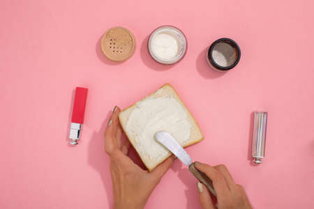 Female hands smear cosmetic cream on a piece of bread for a truck next to cosmetics and jars of supplies on a pink background top view